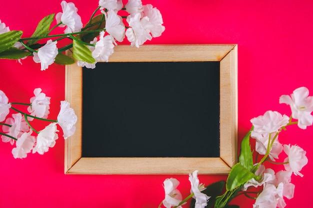 Schoolbord in een houten frame met een lege doos omgeven door witte bloemen