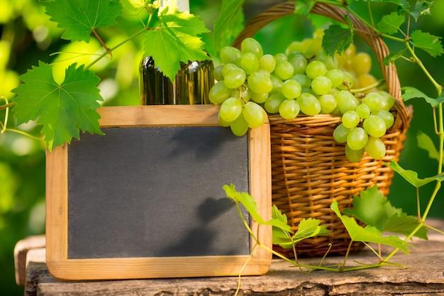 Schoolbord leeg en tros druiven tegen groene lente achtergrond