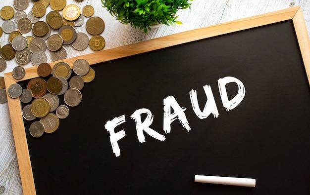 Schoolbord met de tekst fraude en metalen munten op een grijze houten tafel.