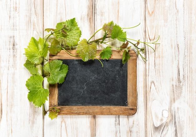 Schoolbord met groene wijnbladeren decoratie op lichte houten achtergrond wooden