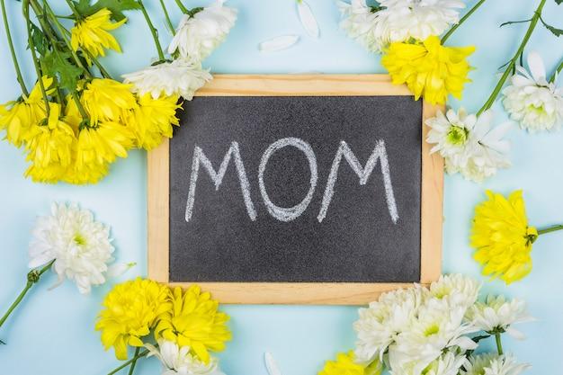 Schoolbord met moedertitel dichtbij bosjes verse bloemen