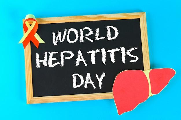 Schoolbord met tekst wereld hepatitis dag. 28 juni. lever en rood geel lint op een blauwe b