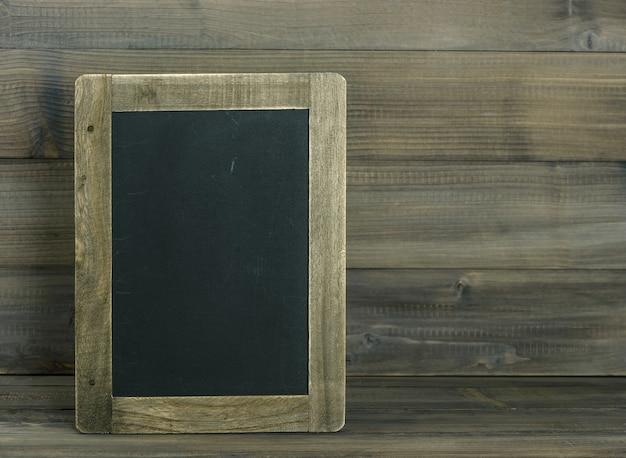 Schoolbord op houten gestructureerde achtergrond. vintage stijl getinte foto