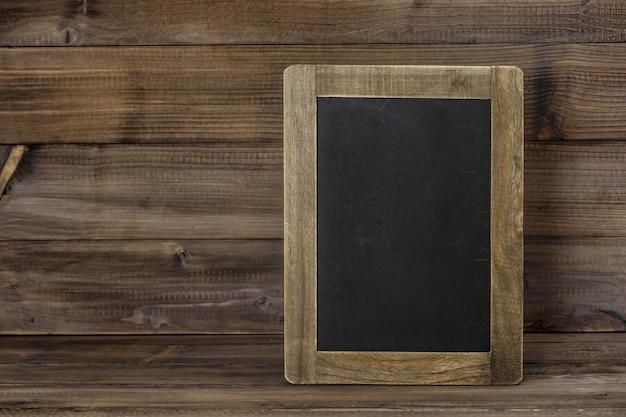 Schoolbord op houten textuur. rustieke achtergrond met kopie ruimte voor uw tekst. vintage stijl getinte foto