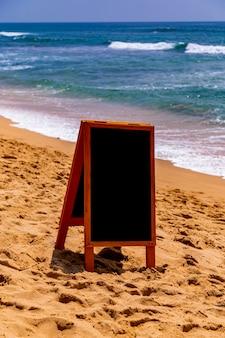 Schoolbord op zandstrand aan de oceaan