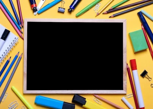 Schoolbord, potloden, markeerstiften, krijtjes op gele tafel