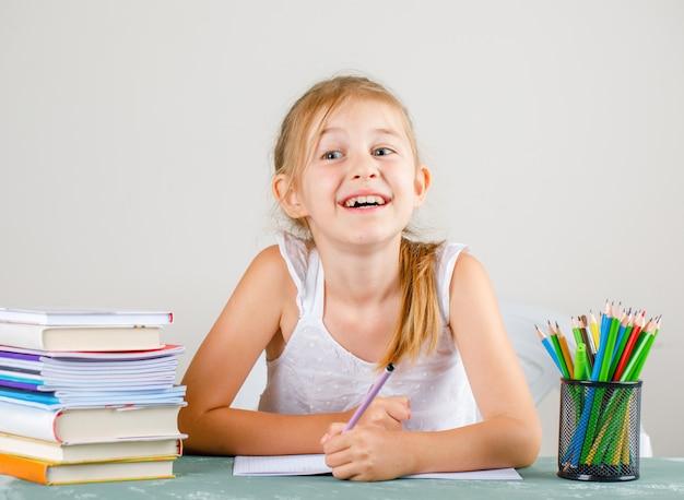 Schoolconcept met potloden, boeken, voorbeeldenboeken zijaanzicht. klein meisje met potlood.