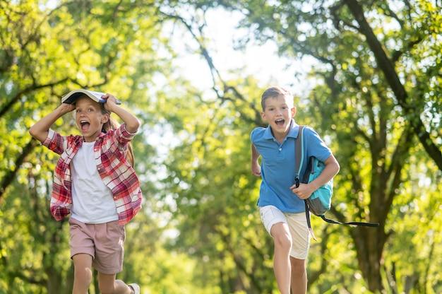 Schoolgaande jongen en meisje die in het park rennen