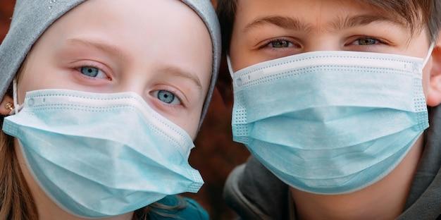 Schoolgaande kinderen in medische maskers. portret van schoolkinderen. Premium Foto
