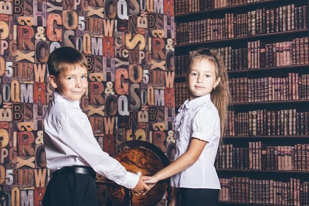 Schoolgaande kinderen overwegen een wereldbol in de bibliotheek