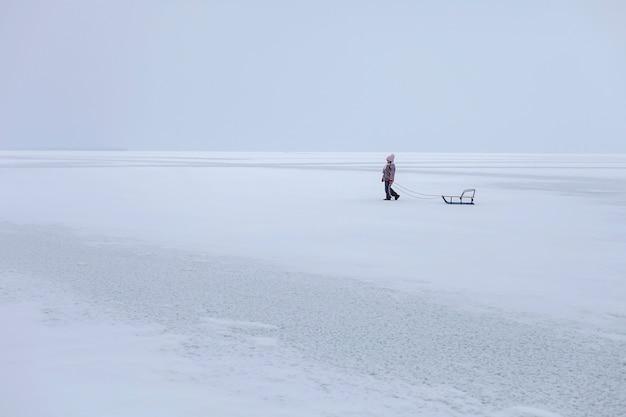 Schoolgaande meisje heeft plezier op het bevroren meer en geniet van een slee rit. winter, stilte en wilde natuur, actief winterweekend, seizoensgebonden buitenactiviteiten, gelukkige gezinslevensstijl, kopie ruimte