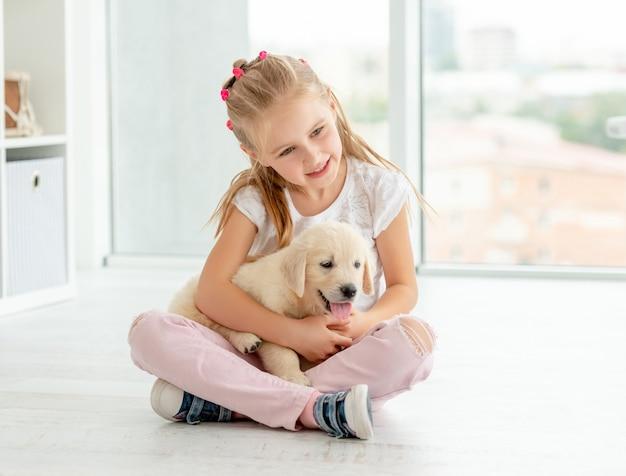Schooljong geitje die zoet puppy koesteren