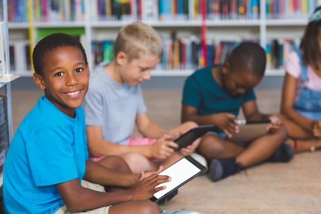 Schooljonge geitjes die op vloer zitten die digitale tablet in bibliotheek gebruiken