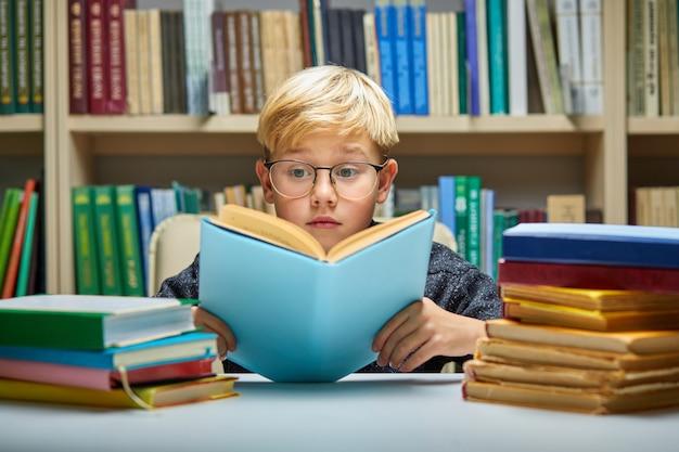Schooljongen aan de tafel zitten en schooltaken doen, omringd door stapels boeken, onderwijs en schoolconcept. hij is verrast door informatie in het boek