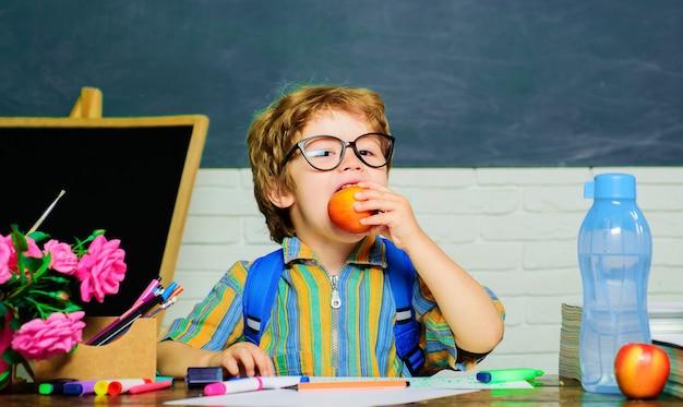 Schooljongen die appel eet. gezond schoolontbijt voor kind. fruitsnack. lunchtijd.