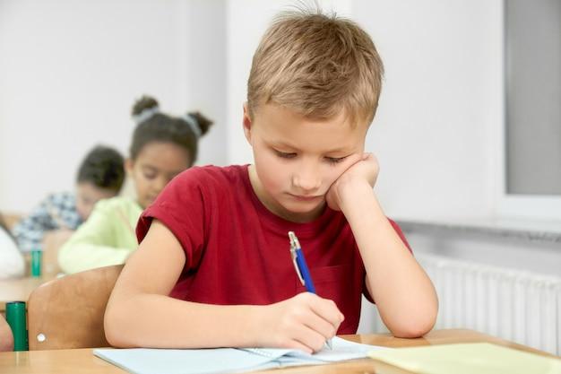 Schooljongen die bij bureau met pen in voorbeeldenboek schrijven.