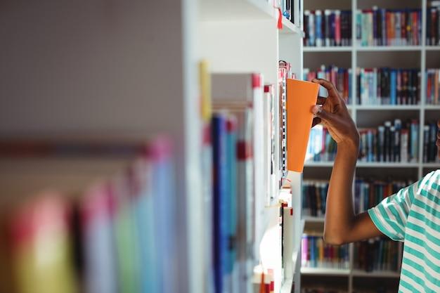 Schooljongen die boek in bibliotheek selecteert