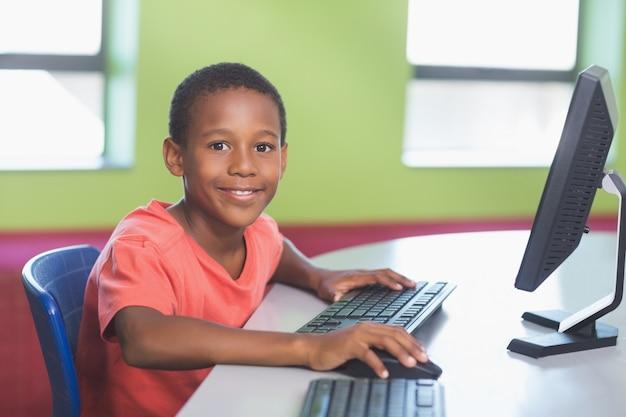 Schooljongen die computer in klaslokaal met behulp van