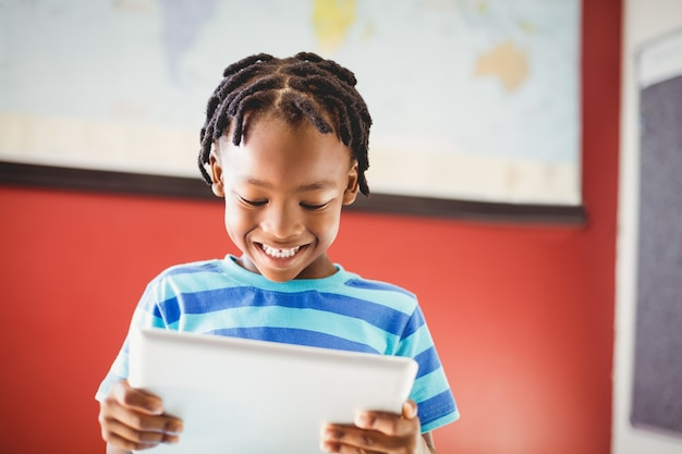 Schooljongen die digitale tablet in klaslokaal gebruiken