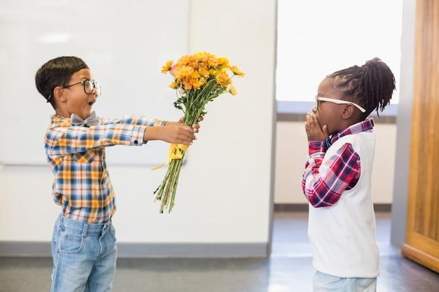 Schooljongen die een bos bloemen geeft aan een meisje