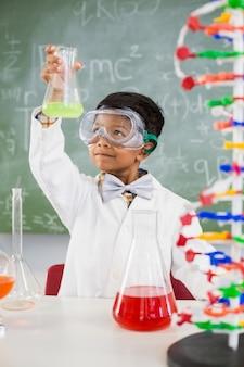 Schooljongen die een chemisch experiment in laboratorium doet