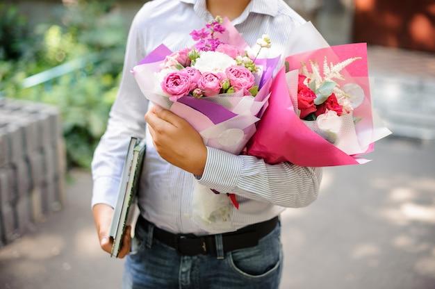 Schooljongen die feestelijk roze boeket twee bloemen houdt