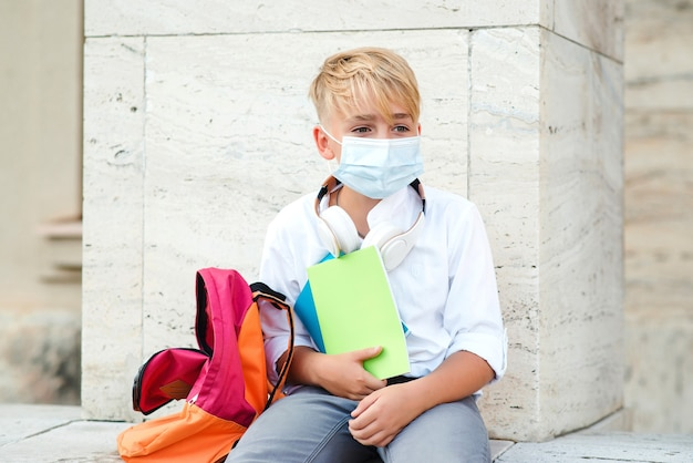 Schooljongen die gezichtsmasker draagt ter bescherming tegen coronavirus.