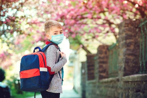Schooljongen die gezichtsmasker draagt tijdens de uitbraak van het coronavirus. terug naar school-concept.