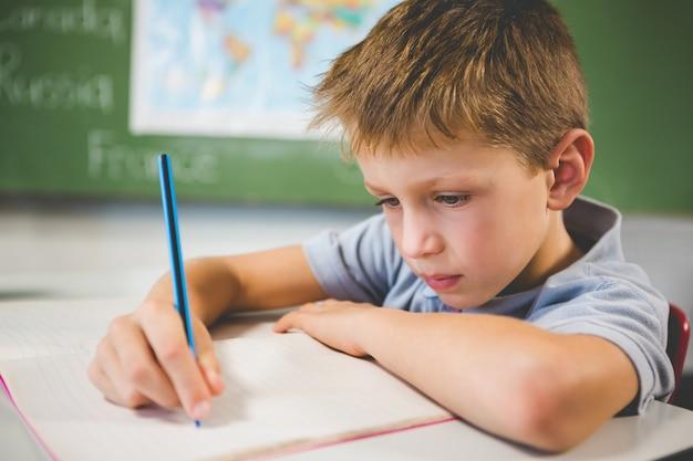 Schooljongen die huiswerk in klaslokaal doet
