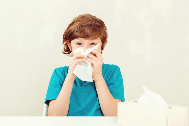 Schooljongen die loopneus blaast. zieke jongenszitting bij bureau. kid met behulp van papieren servetten. allergisch kind, griepseizoen.