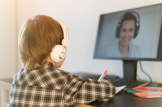 Schooljongen die online cursussen volgt en hoofdtelefoons draagt