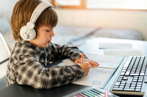 Schooljongen die online cursussen zijaanzicht volgt