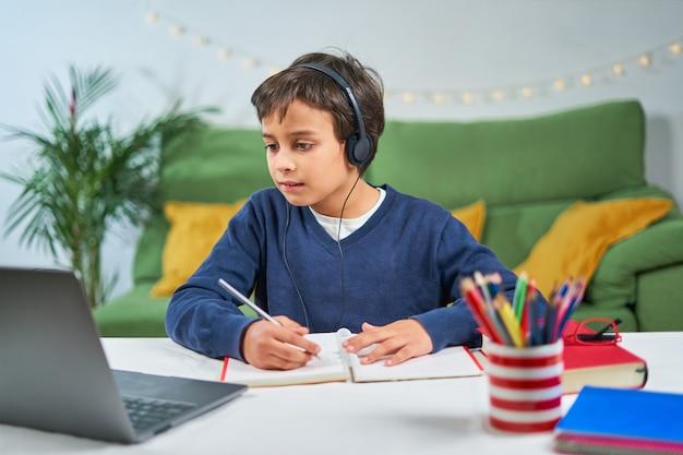 Schooljongen die online lessen heeft terwijl hij thuis in quarantaine zit, laptop gebruikt en notities maakt