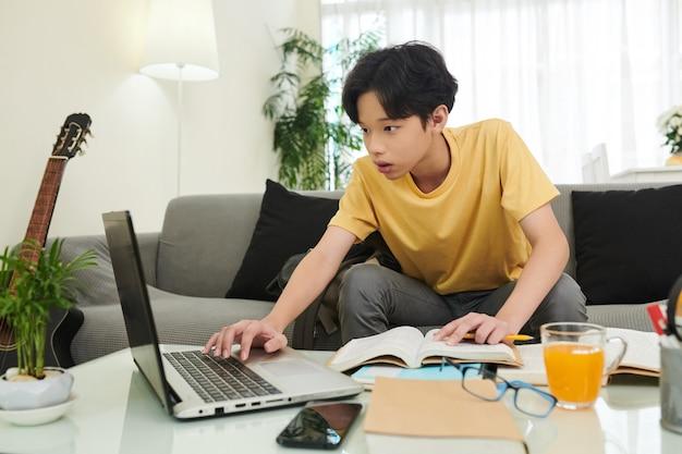 Schooljongen die online naar informatie zoekt