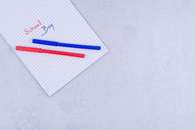 Schooljongen die op papier met blauwe en rode kleuren schrijft.