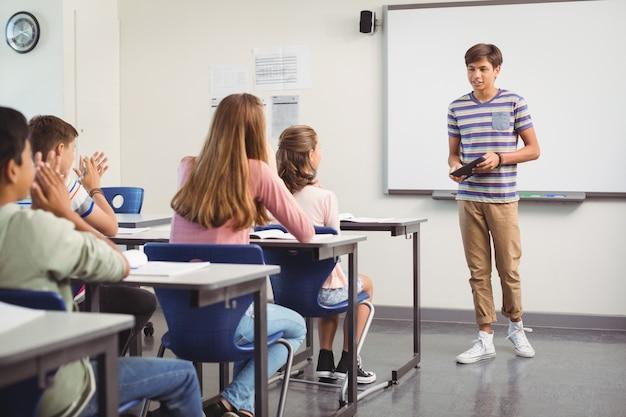 Schooljongen die presentatie geeft in de klas