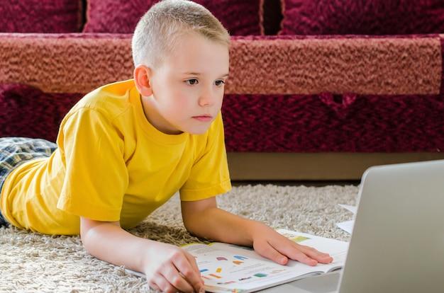 Schooljongen die thuis met laptop bestudeert