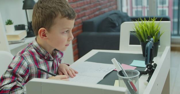 Schooljongen die thuis online op afstand studeert. geconcentreerde kleine jongen jongen met behulp van smartphoneapplicatie, leren op video-klasse.