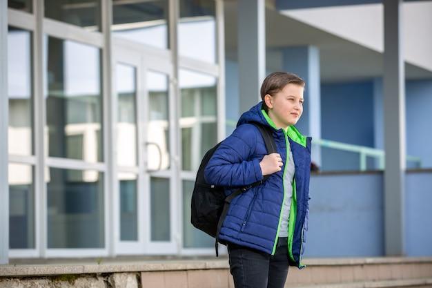 Schooljongen die van school naar huis gaat na het lesgeven, onderwijsconcept