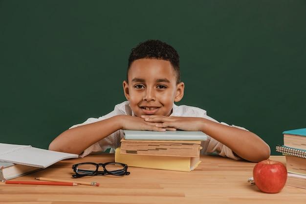 Schooljongen die zijn hoofd op boeken rust