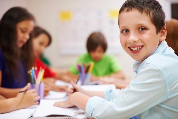 Schooljongen doet zijn huiswerk in de klas