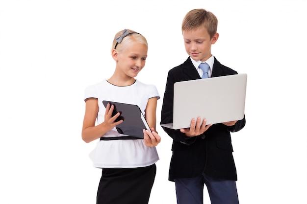 Schooljongen en schoolmeisje met laptop met een tablet op wit