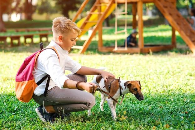 Schooljongen en zijn hond wandelen in het park. vriendschap, dieren en levensstijl. jonge jongen met jack russel terrier buitenshuis. gelukkig man spelen met hond op groen gras.