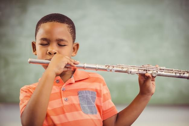 Schooljongen fluit spelen in de klas