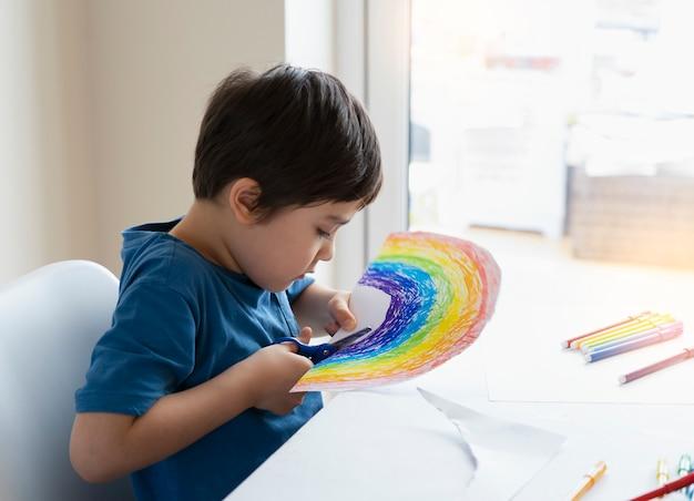 Schooljongen gebruikt schaar die de vorm van vis snijdt voor huiswerk kind dat leert papier te snijden, kind dat thuis blijft, geniet van knutselen