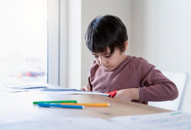 Schooljongen gebruikt schaar die de vorm van vis snijdt voor huiswerk kinderen leren hoe ze papier moeten snijden, kind blijft thuis geniet van knutselactiviteiten