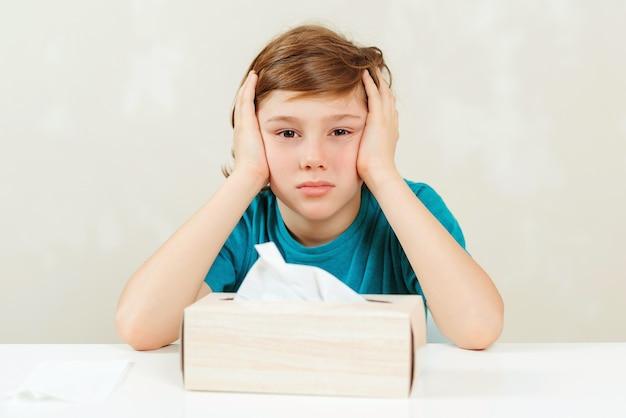 Schooljongen heeft hoofdpijn tijdens lessen. zieke jongen zit aan het bureau.