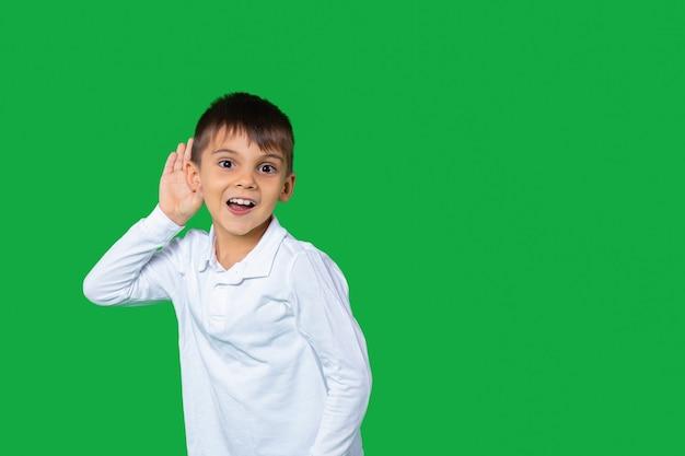 Schooljongen houdt hand in de buurt van oor grappige jongen luistert aandachtig