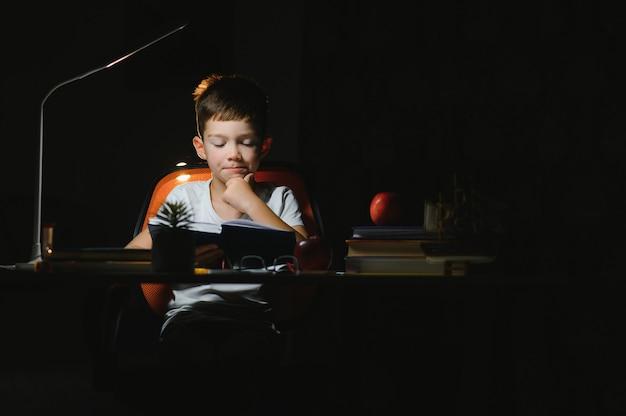 Schooljongen huiswerk aan de tafel in zijn kamer.