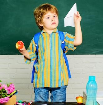 Schooljongen in de klas met papieren vliegtuigje. basisschooljong geitje bij bureau. opvoeden en leren.